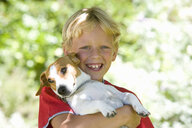 Boy (6-8) with dog outdoors, smiling, portrait - JUIF00283