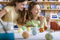 Young girls decorating Easter eggs - JUIF00304