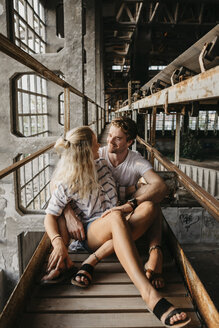 Happy young couple sitting in an old train station - LHPF00512