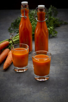 Carrot juice in bottles and glasses, bunch of carrots - LVF07911