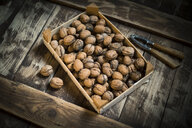 Walnuts in wooden box and nutcracker, wooden background - MAEF12827