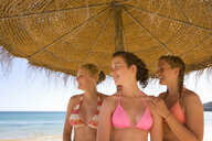 Teenage girls posing under beach umbrella - JUIF00387