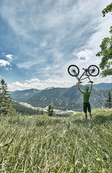 Germany, Bavaria, Isar Valley, Karwendel Mountains, mountainbiker on a trip lifting up his bike on alpine meadow - WFF00071
