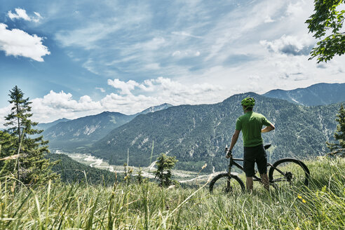 Germany, Bavaria, Isar Valley, Karwendel Mountains, mountainbiker on a trip having a break on alpine meadow - WFF00074