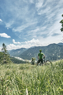 Germany, Bavaria, Isar Valley, Karwendel Mountains, mountainbiker on a trip having a break on alpine meadow - WFF00077
