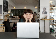 Frustrated young woman using laptop in a cafe - FLLF00066