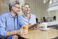 Happy woman and man using tablet in a cafe - PNEF01387