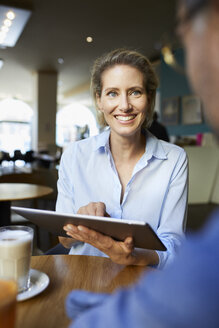 Smiling woman and man with tablet in a cafe - PNEF01396