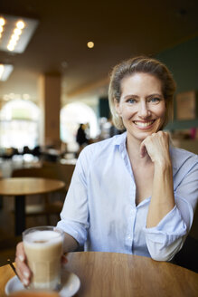 Portrait of smiling woman in a cafe - PNEF01399