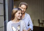 Portrait of happy mother with daughter at open door - PNEF01414