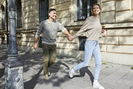 Happy couple running on pavement in the city - PNEF01423
