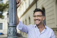 Portrait of happy businessman leaning against lamp post in the city - PNEF01435