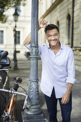 Portrait of smiling businessman with bicycle leaning against lamp post in the city - PNEF01438