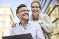 Happy couple using tablet in the city - PNEF01450