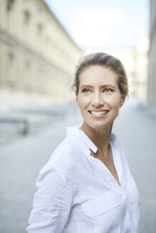 Portrait of smiling woman wearing white shirt in the city - PNEF01453