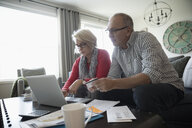 Senior couple with credit card and laptop paying bills online in living room - HEROF31485