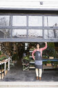 Portrait female shop owner opening garage door in plant shop - HEROF31515