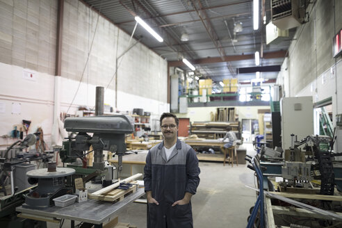 Portrait confident male carpenter at drill press in workshop - HEROF31524