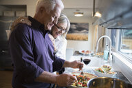 Senior couple cooking and drinking wine in kitchen - HEROF31560