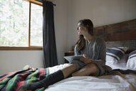 Woman using digital tablet on bed looking out the window - HEROF31682