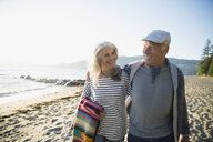 Smiling senior couple walking on sunny beach - HEROF31712