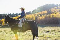 Woman sitting horseback in sunny autumnal field - HEROF31727