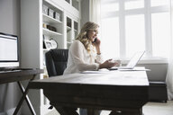 Woman working in home office talking on cell phone - HEROF31742