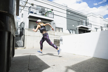 Young woman running in sunny urban alley - HEROF31772