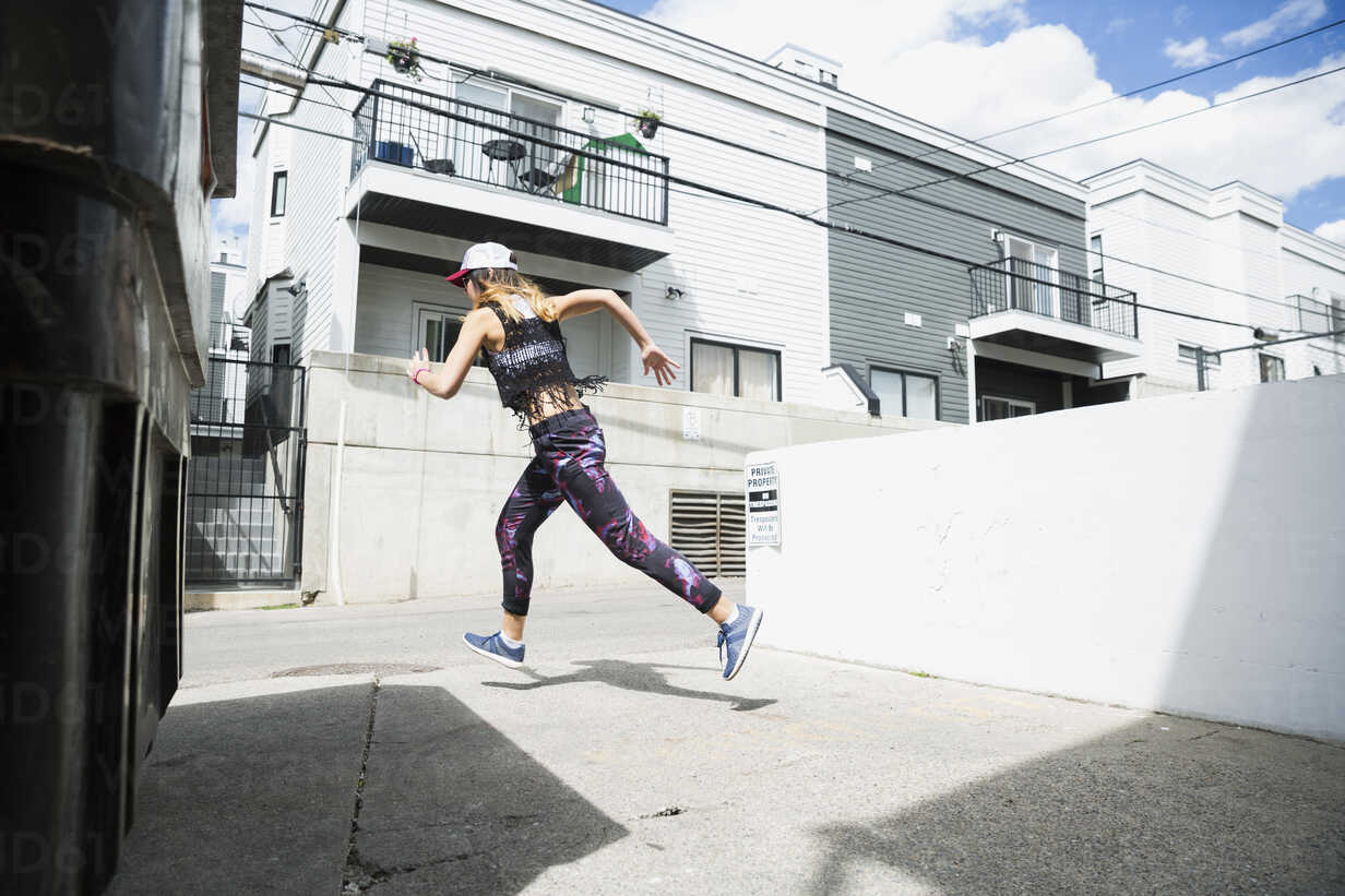 Young woman running in sunny urban alley - HEROF31772 - Hero Images/Westend61