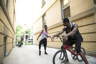 Young man on BMX bicycle watching woman dancing in urban alley - HEROF31775