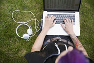 Young woman with tattoos using laptop in grass with headphones - HEROF31778