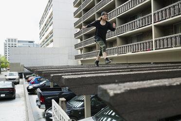 Young man free running on carport roof below urban apartment buildings - HEROF31781