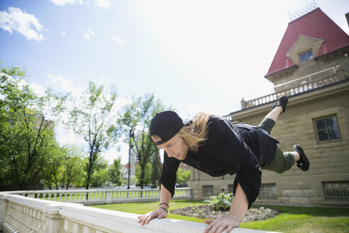 Young man doing parkour on railing in sunny garden - HEROF31784