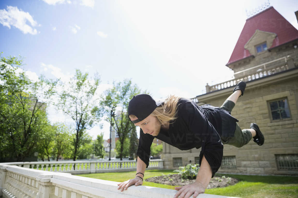 Young man doing parkour on railing in sunny garden - HEROF31784 - Hero Images/Westend61