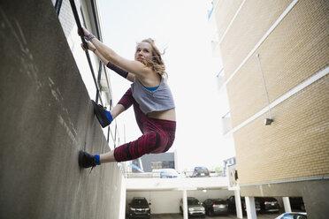 Young woman doing parkour along urban wall - HEROF31787