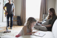 Young family reading and vacuuming in living room - HEROF31793