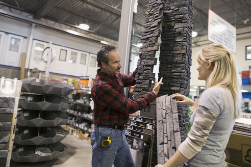 Worker assisting woman at stone column in home improvement store - HEROF31829