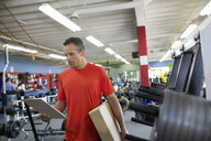 Worker with clipboard in home gym equipment store - HEROF31838