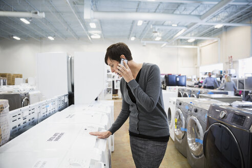Woman talking on cell phone shopping for clothes washer in appliance store - HEROF31850