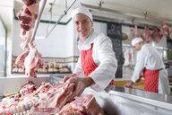 Smiling butcher arranging meat in display case - JUIF00454