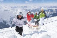 Smiling family pulling sled in snow on ski slope - JUIF00484