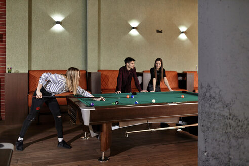 Young woman playing billiards with friends - ZEDF02025