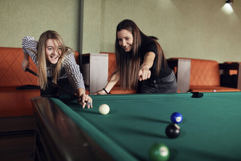 Two happy friends playing billiards together - ZEDF02028