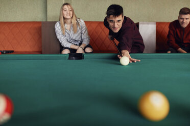 Man playing billiards watched by friends - ZEDF02037