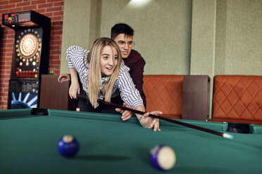 Young man guiding girlfriend at billiard table - ZEDF02040