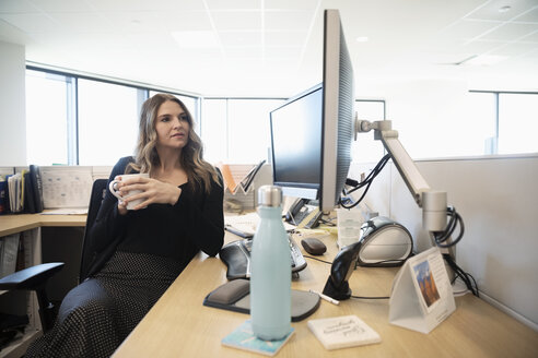 Businesswoman drinking coffee at computer in office cubicle - HEROF31867