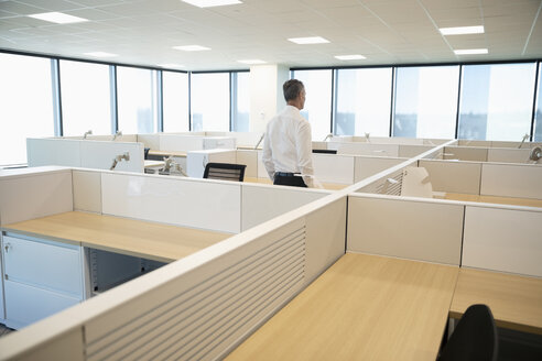 Businessman standing among cubicles in new office - HEROF31876
