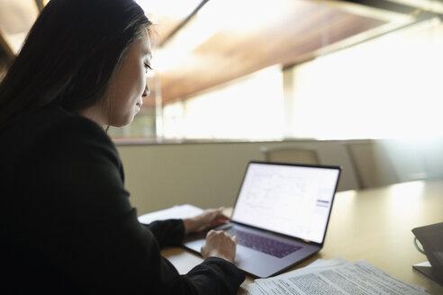 Focused businesswoman using laptop in office - HEROF31921