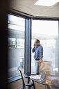 Businessman talking on smart phone in conference room - HEROF31957