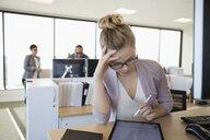 Focused businesswoman using digital tablet with stylus in office - HEROF31972